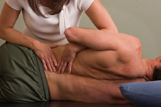 Physical therapist applying manual therapy to a clients lower back muscles