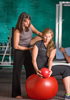 Physical therapist works with client on a medicine ball to prepare for surgery